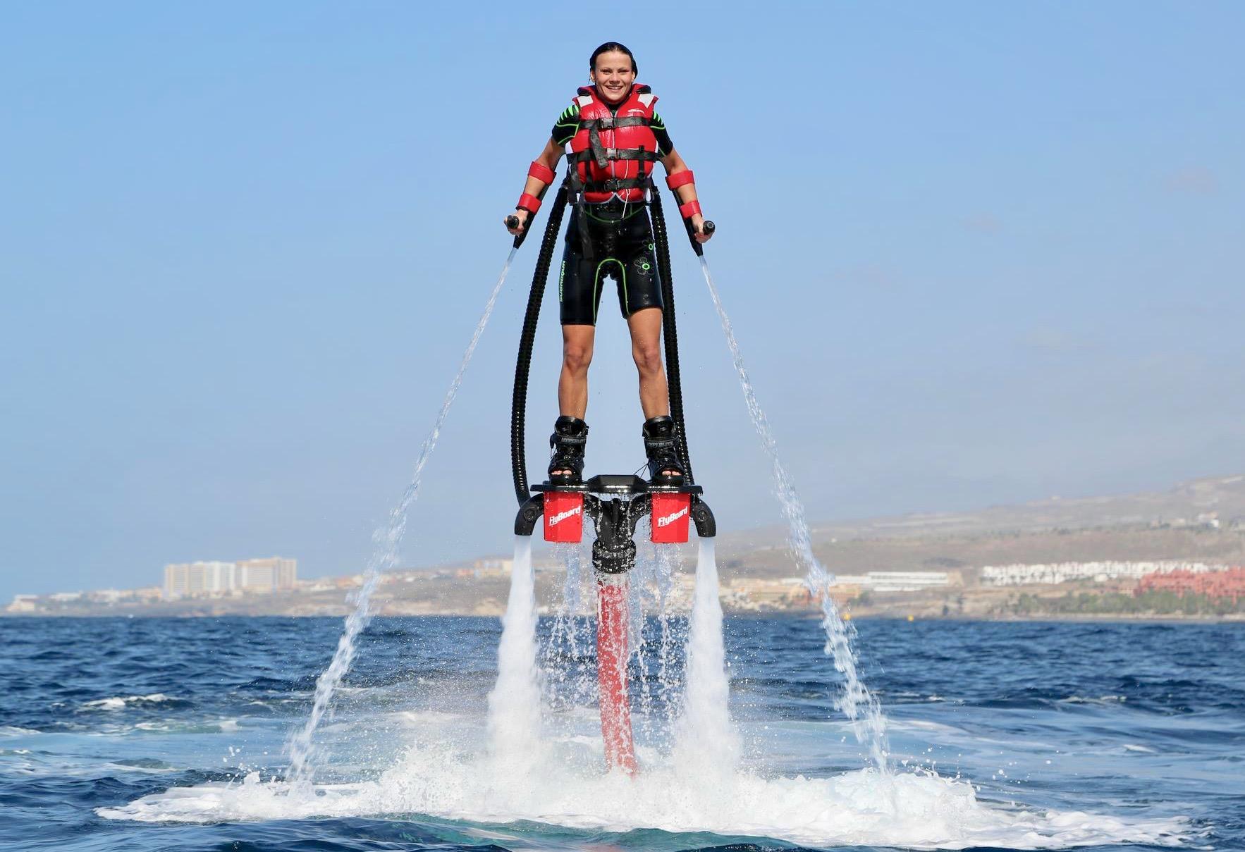 Una chica probando el flyboard y está flotando sobre el agua como Iron Man.