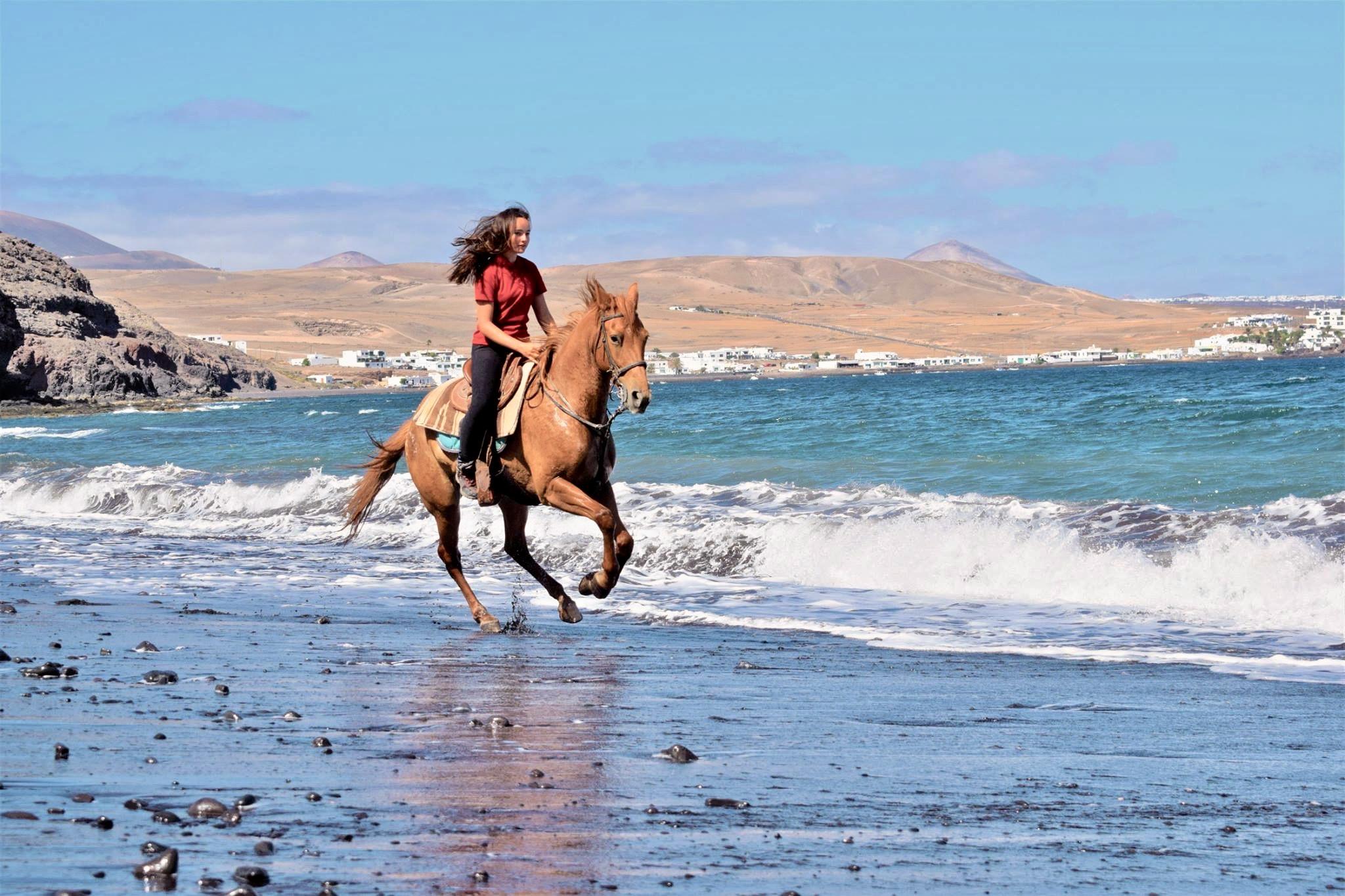 Una niña galopando en caballo en una playa con un paisaje pintorezco de volcanes y casas blancas al fondo.