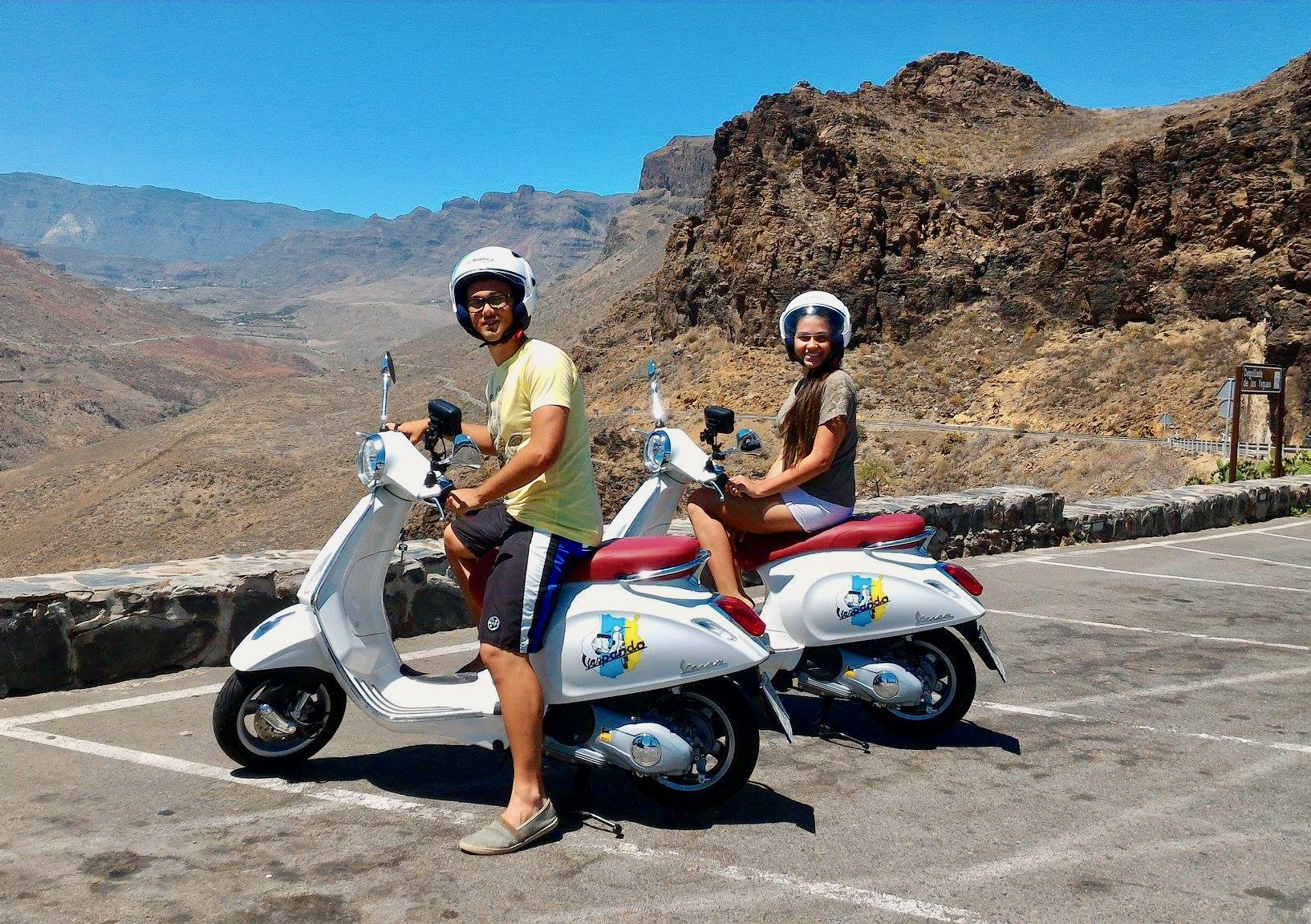 Una joven pareja en scooters se detiene para una sesión de fotos en un mirador.