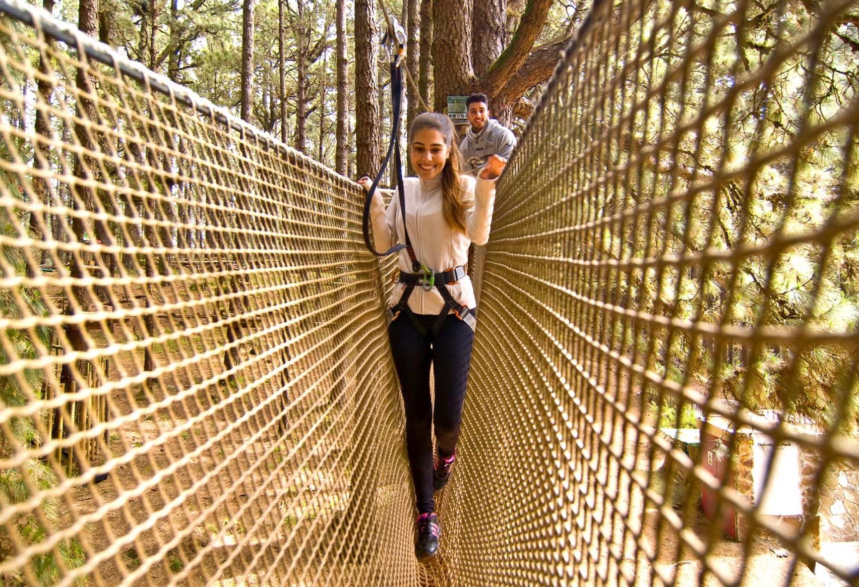 Una niña sonriendo mientras cruza una red de obstáculos al aire libre