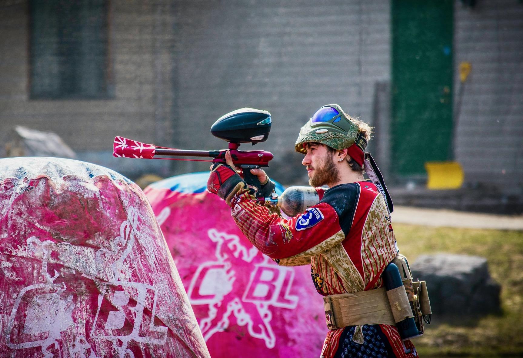 Un hombre vestido con ropa protectora está apuntando con su pistola de paintball listo para disparar.