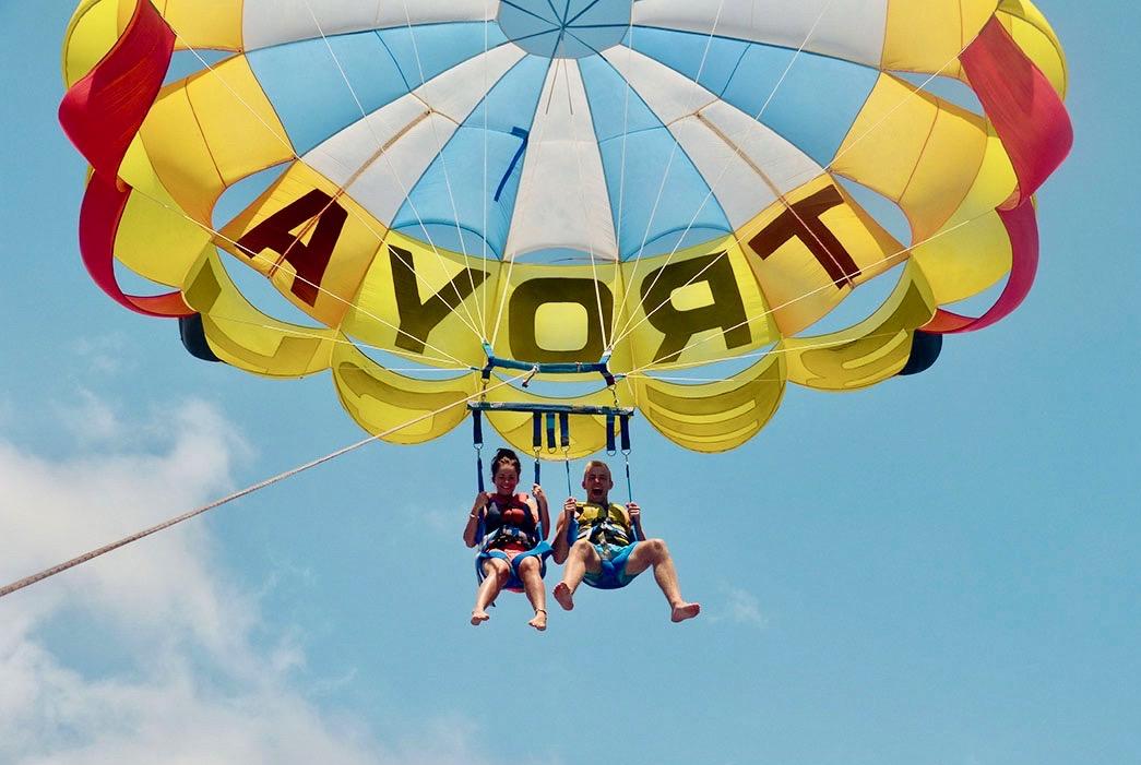 Dos amigos gritando y riendo en un vuelo en parapente