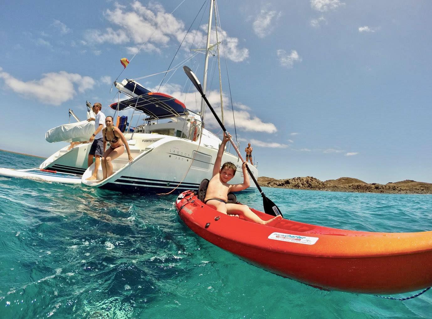 Una pequeña familia disfrutando en el agua y en un kayak durante su excursión en un catamarán de alquiler privado.