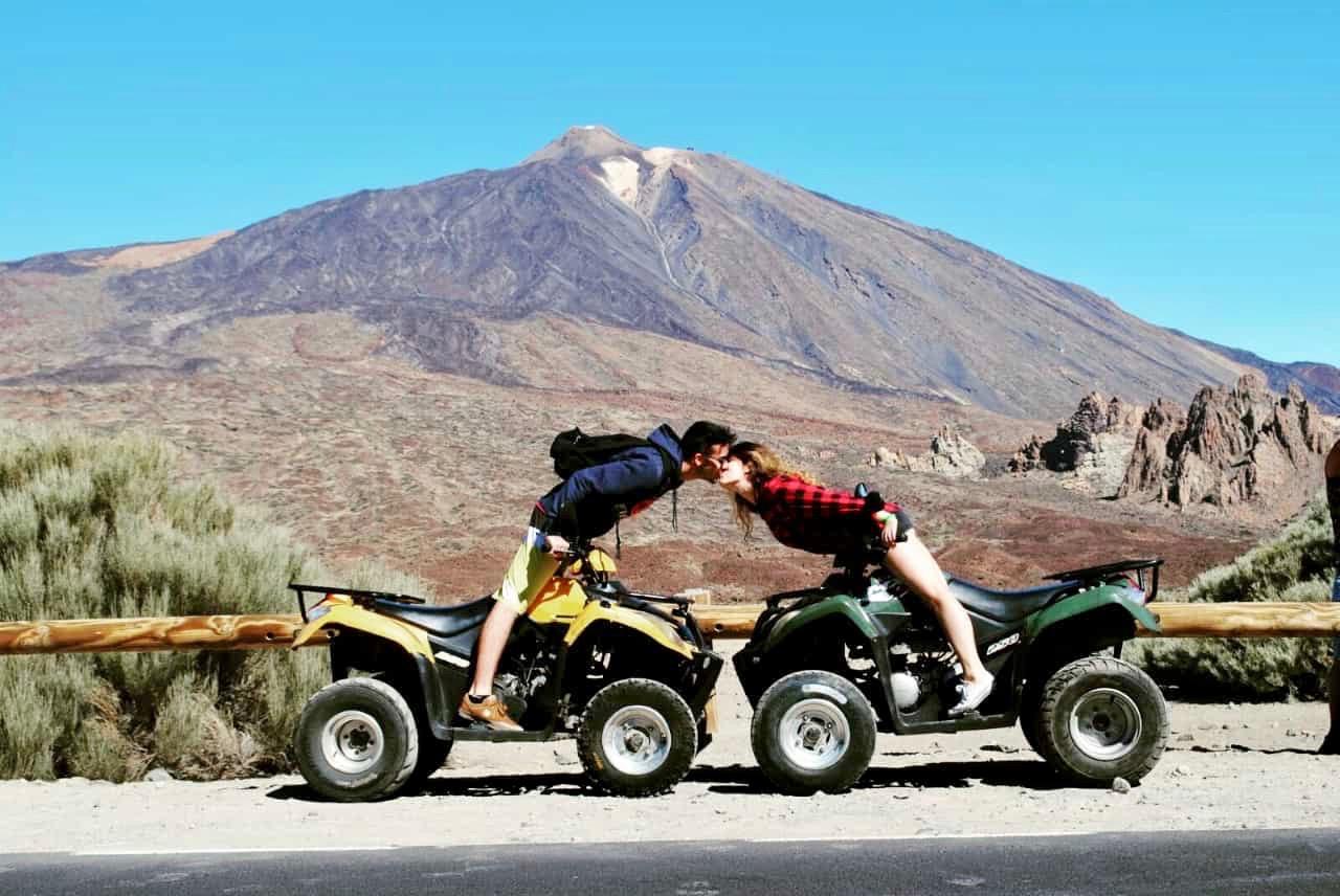 Una pareja con su quad uno frente al otro, besándose y posando para la foto frente al bello volcán Teide.