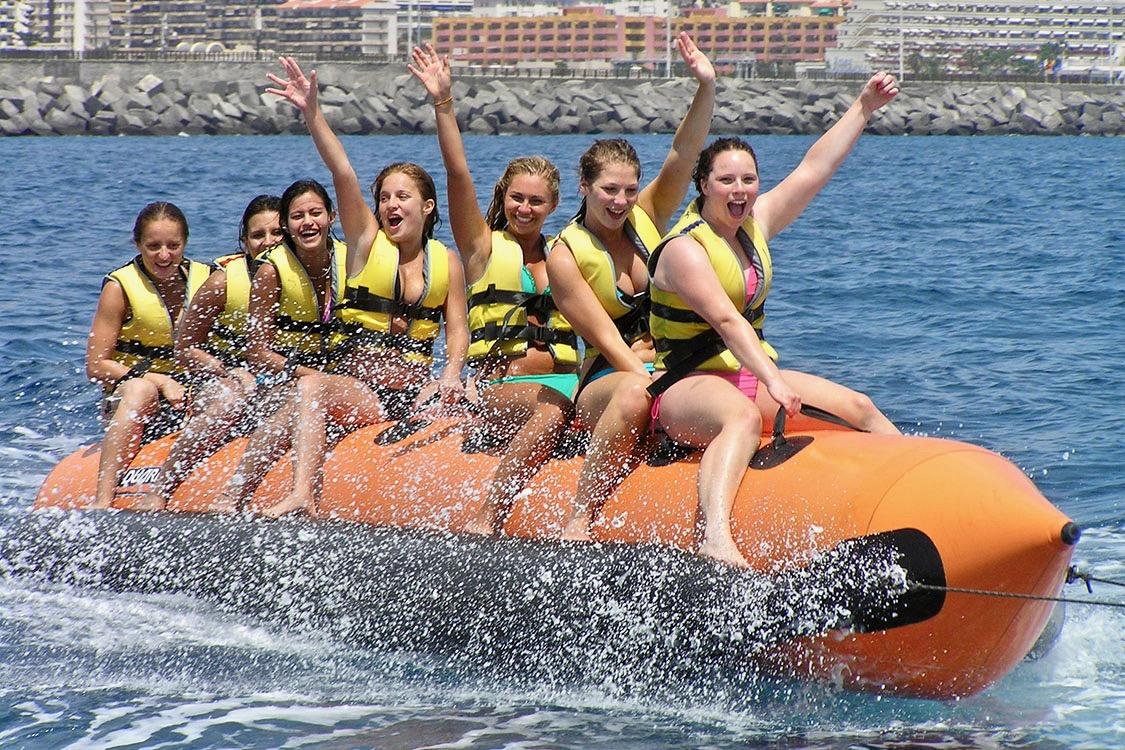 Un grupo de niñas saludando y riendo mientras su banana boat avanza a toda velocidad por el agua.
